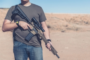 Man on desert range posing with assault rifle, AR-15